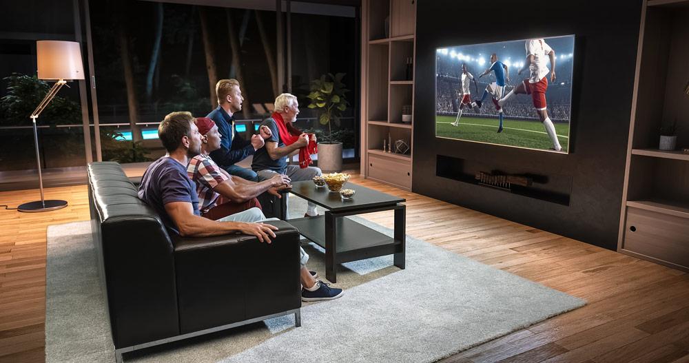 Cuatro hombres mirando un partido de fútbol en televisor de pantalla plana