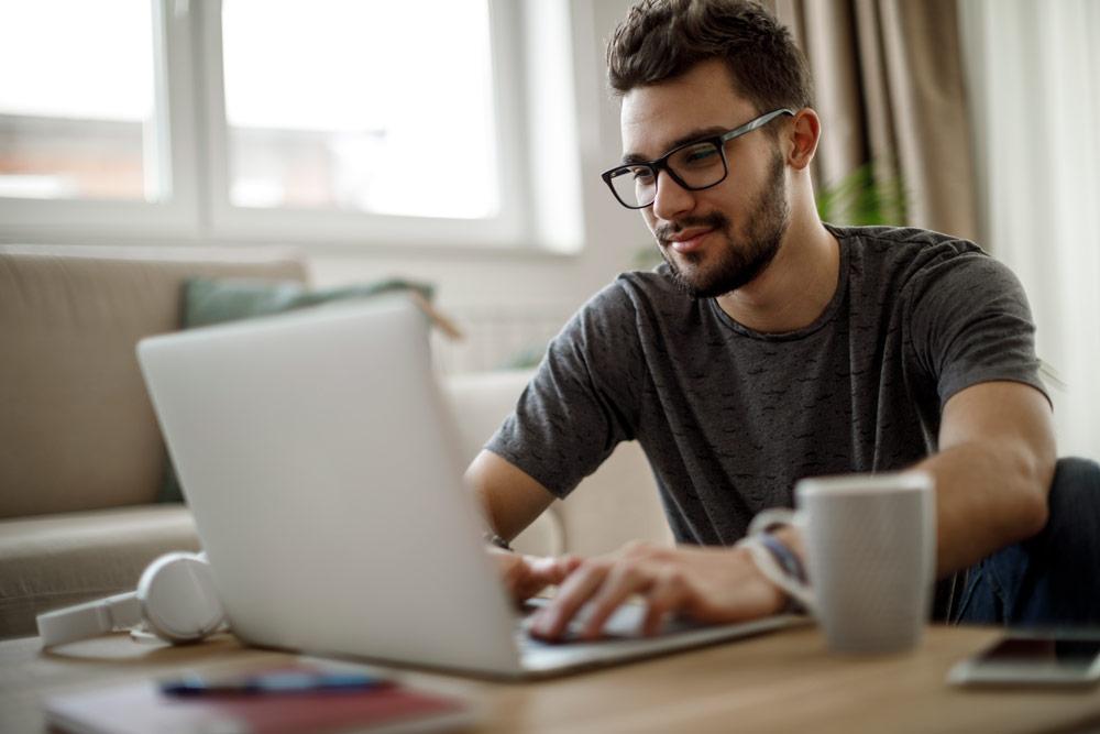 Hombre joven con anteojos trabajando con una computadora portátil
