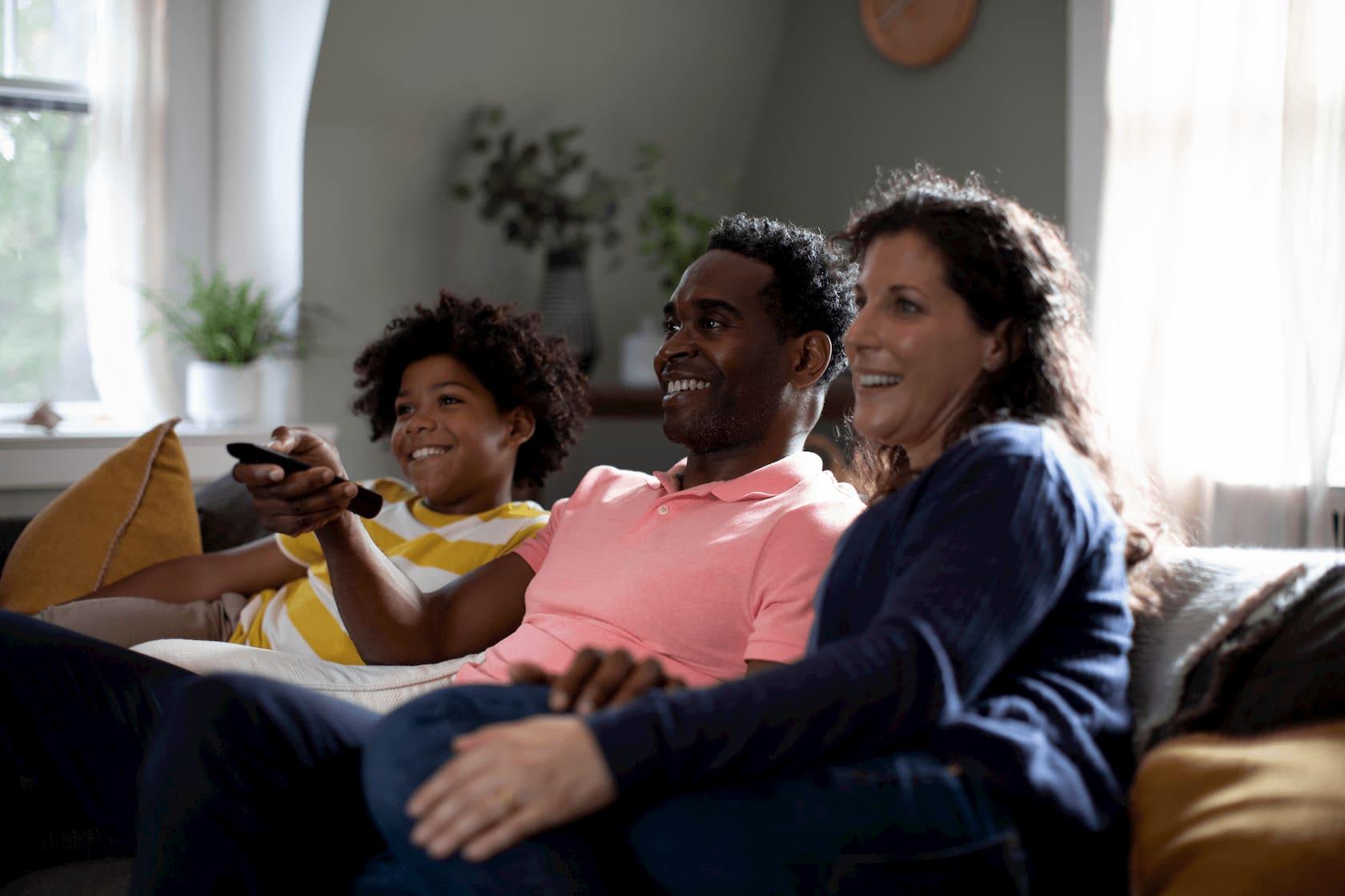 Foto de una familia emocionada sentada en una sala iluminada, usando el control remoto, preparados para ver una película en su televisor.