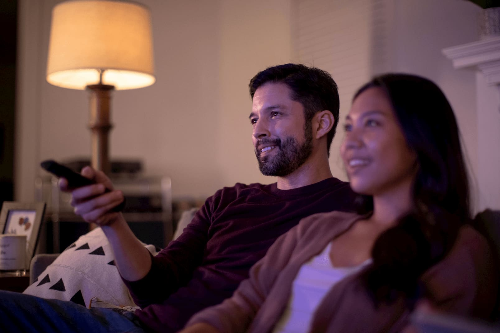 Foto de una pareja feliz sentada en una sala, usando el cotrol remoto y preparándose para ver una película en su televisor.