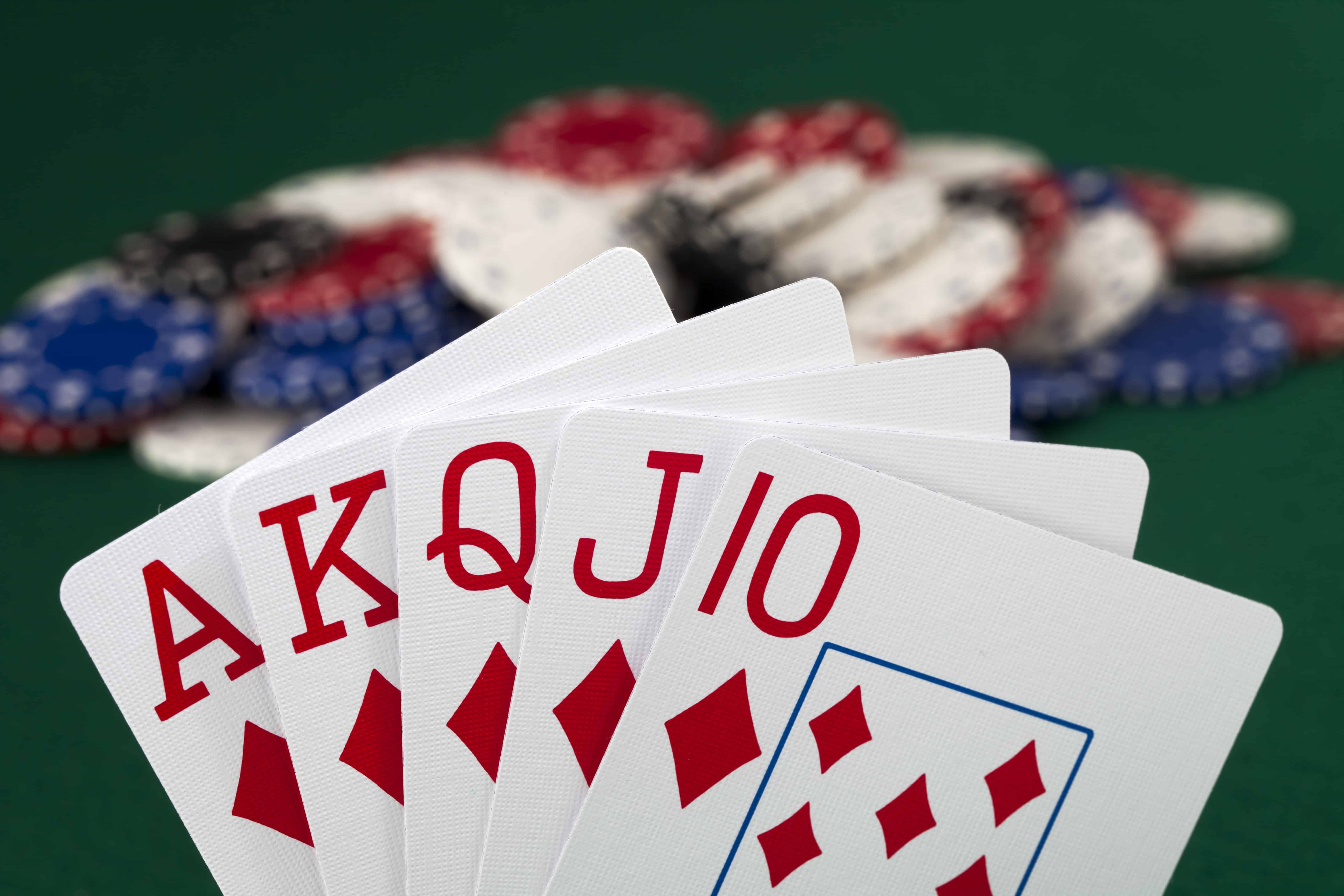 Close up of a five cards aligned in a fan as a hand of 5-card stud, with poker chips resting on a felt table in the background, some of the cards have been replaced with smart phone models