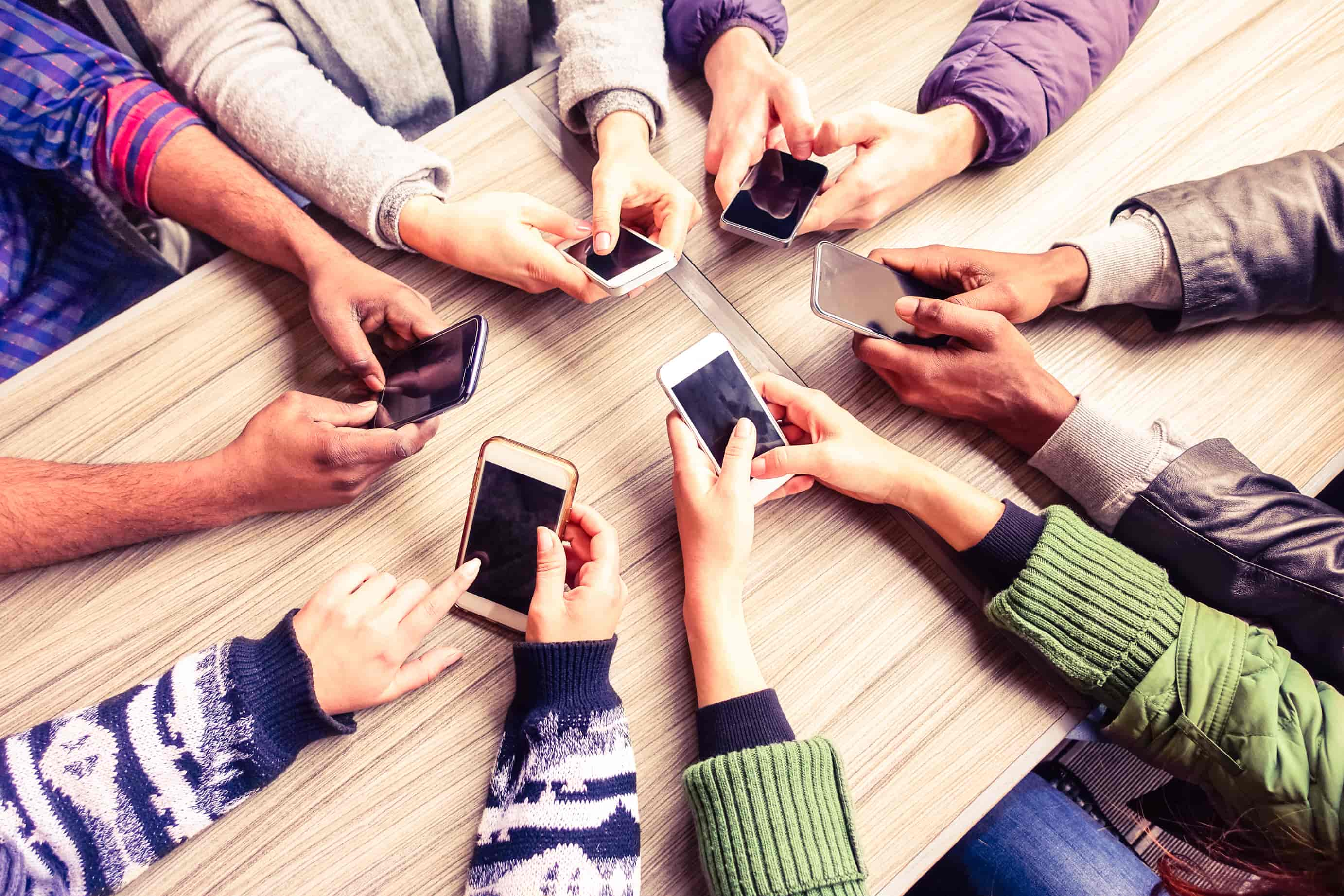 Close up photograph from an elevated perspective looking down on a group of people comparing mobile devices - their arms and hands arrayed in a circle, each holding a different device in the center, all resting on a table top