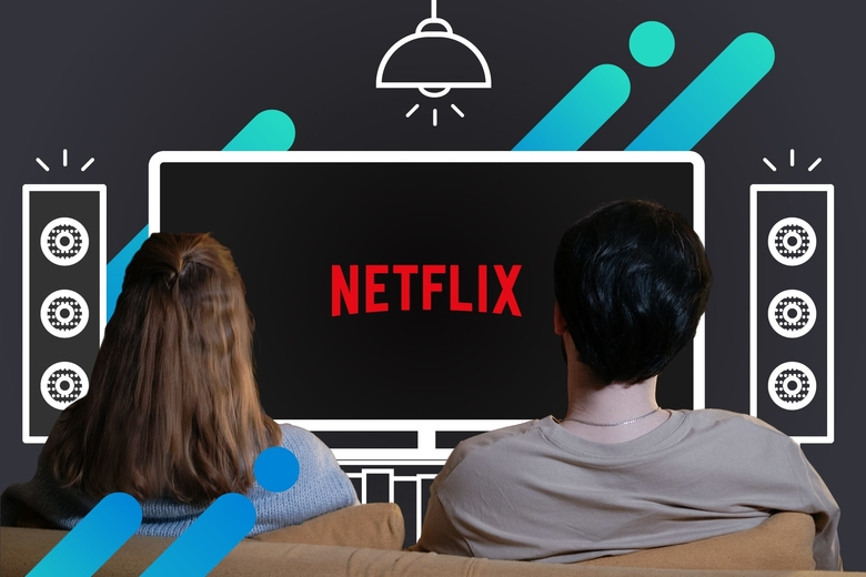 Pareja sentada en un sillón cómodo, vista desde atrás, mirando una configuración imaginaria de cine en casa con un televisor de pantalla grande y altavoces, con el logo de Netflix en la pantalla.