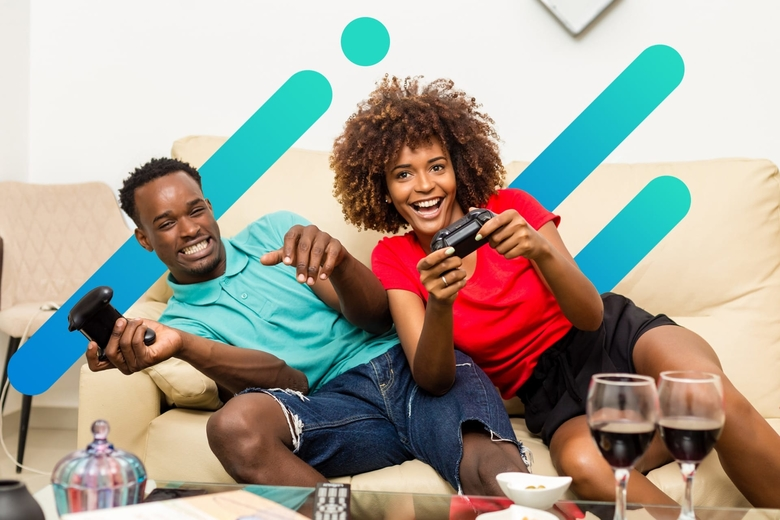 A happy African American couple sits on their living room couch, both holding a controller and smiling while playing a video game
