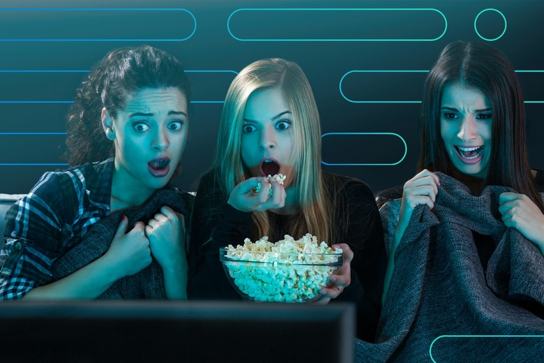 Three teenage girls grimace in fright while watching a horror movie with a large bowl of popcorn.