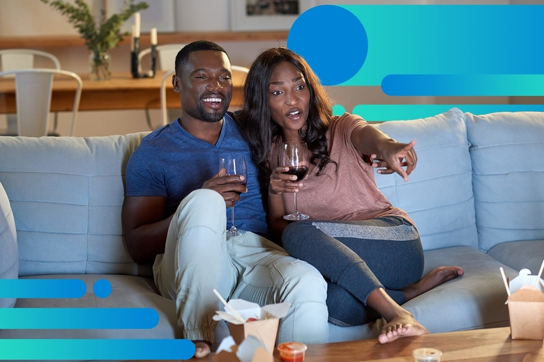 An African American couple smiles while watching a TV show on their couch, each is holding a glass of red wine