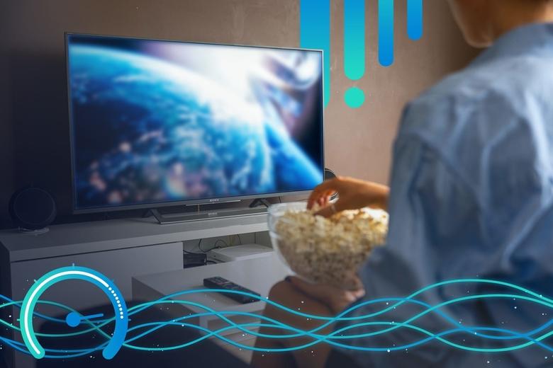 Foto de una mujer sentada en un sillón con un bowl de palomitas de maíz frente a un televisor de alta definición que muestra una película en un servicio de streaming