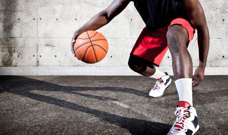 Basketball player dribbling with agressive stance ready to charge