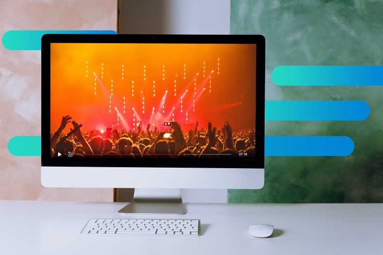 Photo of a desktop computer with wireless keyboard and mouse, the monitor displays footage of a concert available for streaming, with Optimum graphic overlays