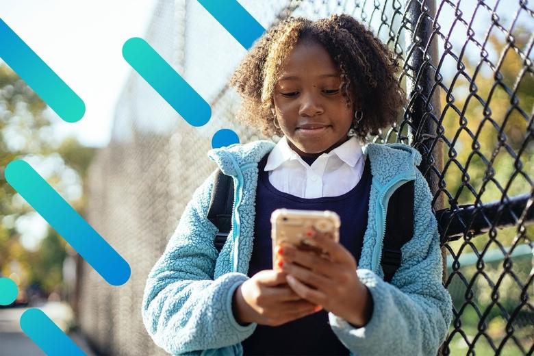 Niña usando un teléfono inteligente en el parque