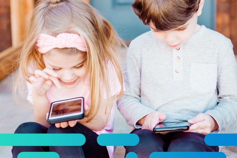 Dos niños usando teléfono móviles