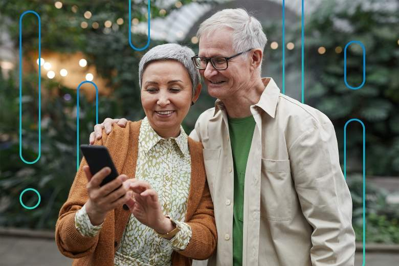 older couple smiling while looking at something on their smartphone