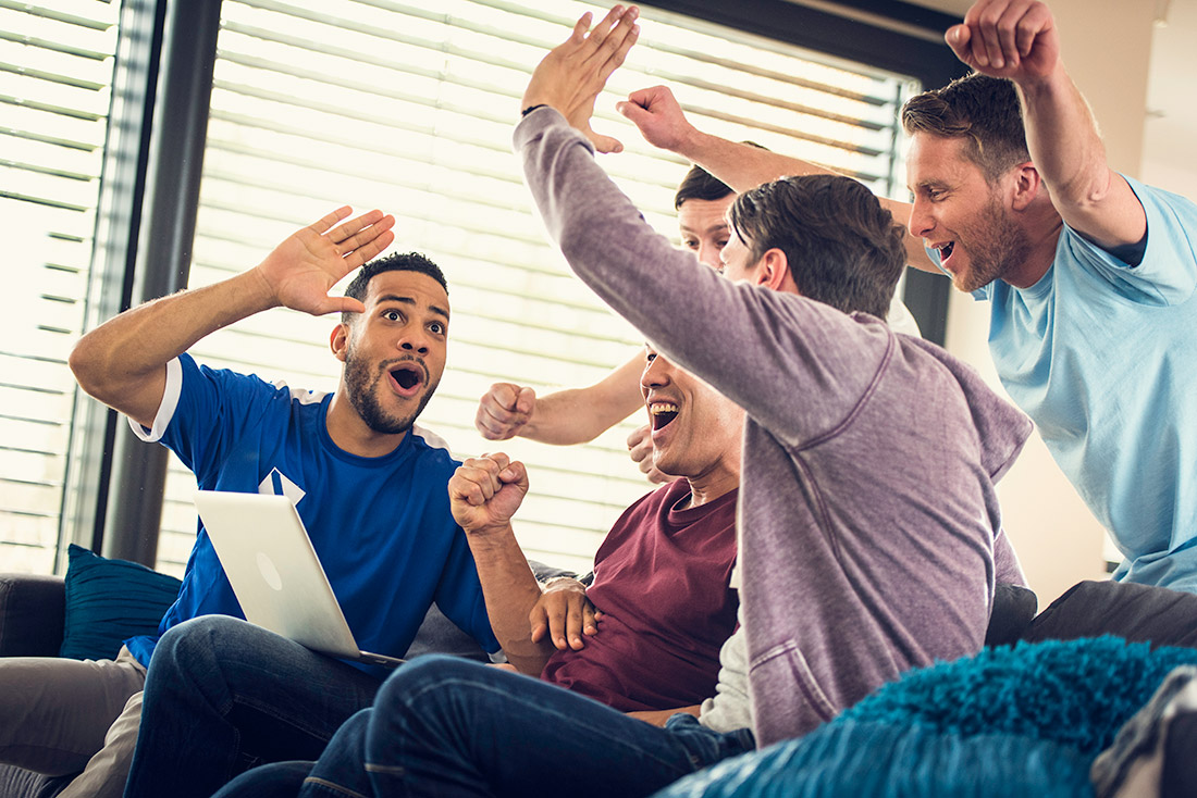 ​​Five friends celebrating score while watching sports game