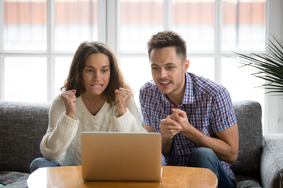 Excited couple watching game on laptop