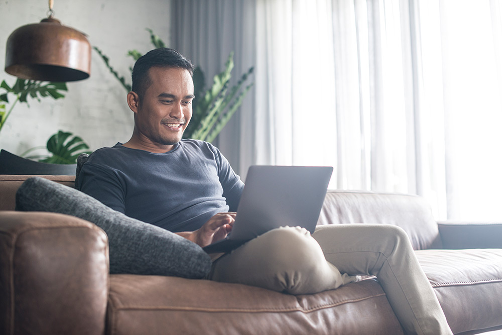 Man sitting on couch while smiling at laptop