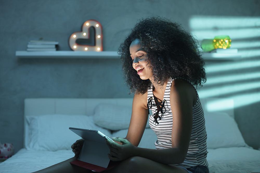 Mujer con una tablet sentada en la cama
