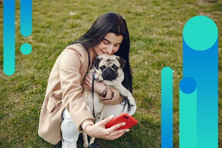 woman taking a selfie with her dog on an iphone