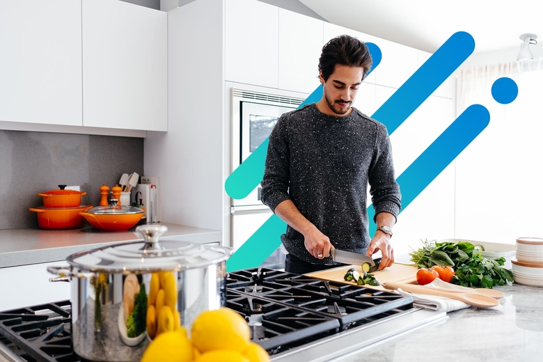 Man prepping food to cook in a modern kitchen on abstract background